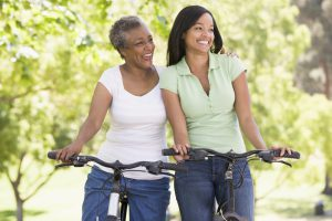 Two women on bikes outdoors smiling