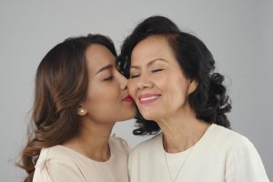 Asian young woman kissing her middle-aged mother